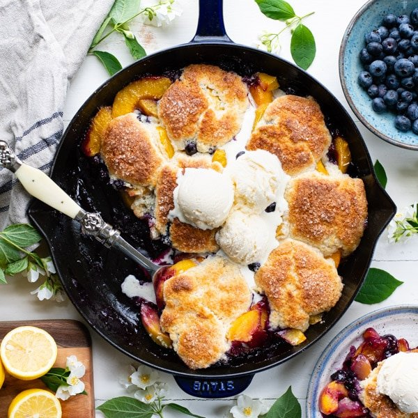 Square overhead image of peach blueberry cobbler recipe baked in a cast iron skillet