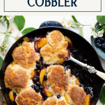 Close overhead image of old fashioned peach and blueberry cobbler with text title box at top