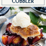 Close up side shot of a serving of peach blueberry cobbler with text title box at top