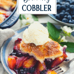 Close up side shot of an old fashioned peach and blueberry cobbler with text title overlay