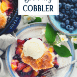 Overhead shot of a plate of peach and blueberry cobbler with text title overlay