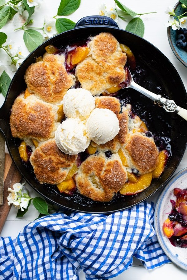 Overhead image of a skillet of Southern peach blueberry cobbler on a white table with a blue and white cloth napkin