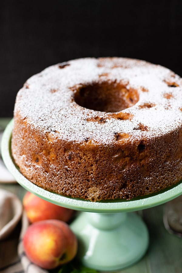 Close up shot of powdered sugar on top of a peach pound cake