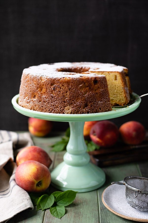 Peach pound cake on a green cake stand with fresh peaches nearby