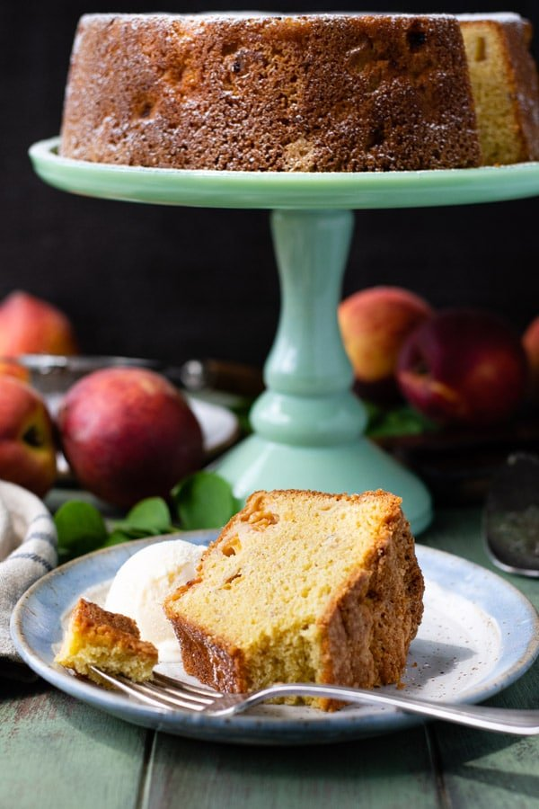 Side shot of a bite of peach pound cake on a fork on a plate