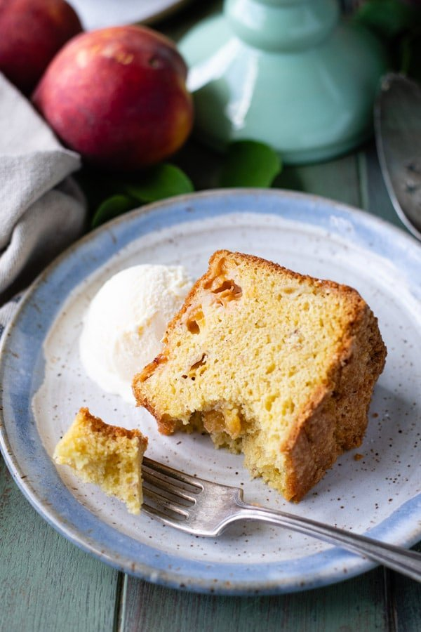 Slice of peach pound cake on a plate with ice cream