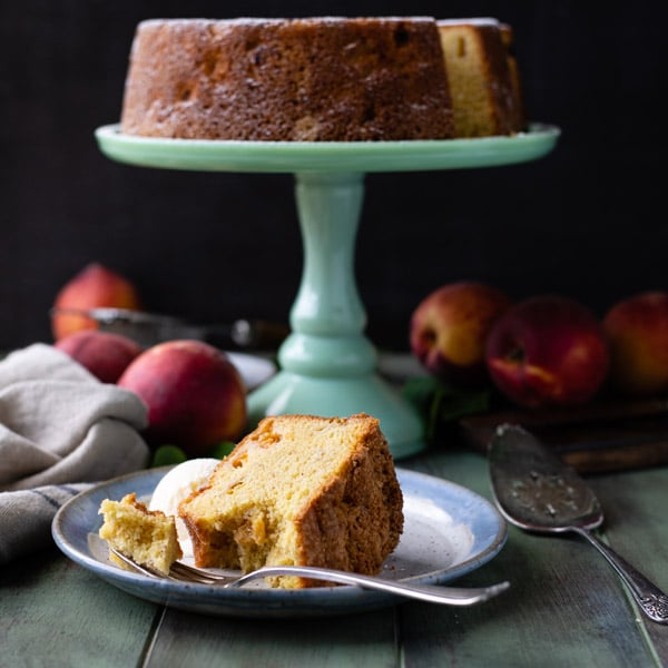 Side shot of a slice of peach pound cake on a plate in front of the cake stand