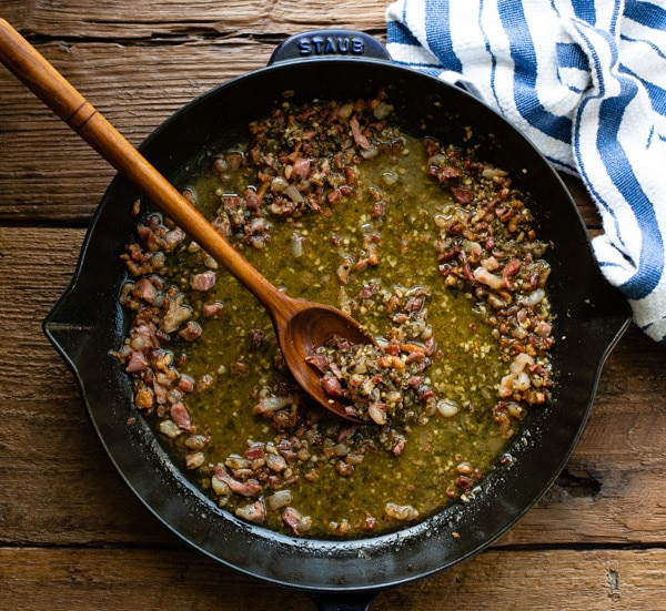Pesto sauce in a skillet with pancetta
