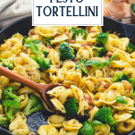 Side shot of pesto tortellini in a skillet with text title overlay