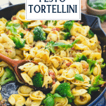 Close up side shot of a skillet of fresh basil pesto tossed with cheese tortellini and text title overlay