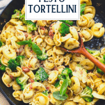 Close overhead shot of pesto tortellini pasta with text title overlay