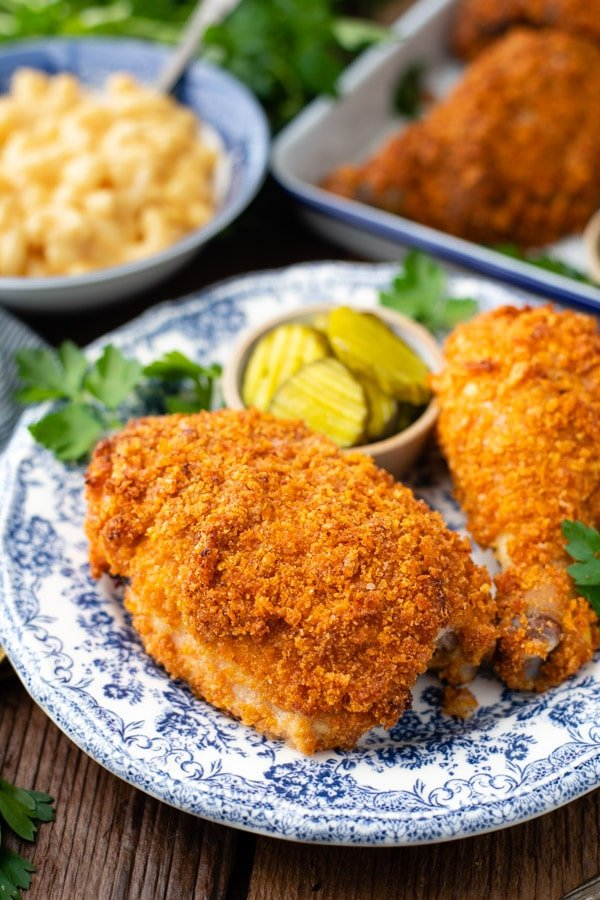 Close up shot of a plate of Southern oven fried chicken with a side of pickles