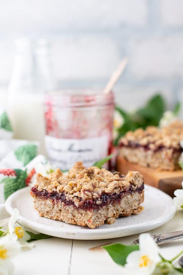 Side shot of a single raspberry oatmeal bar on a white plate