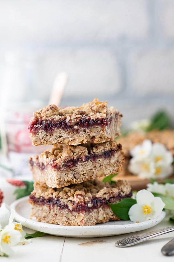 Side shot of three raspberry jam crumble bars on a plate with flowers nearby