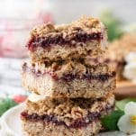 Close up side shot of a stack of three raspberry crumble bars on a white plate