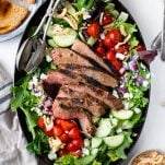 Overhead image of grilled steak salad recipe on a large serving platter with a side of bread