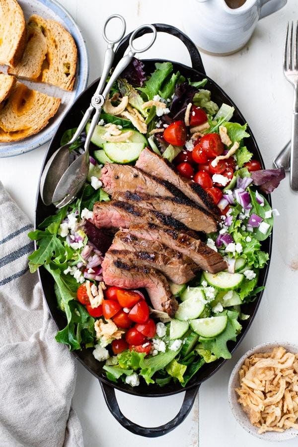 Overhead shot of summer steak salad served with balsamic dressing.