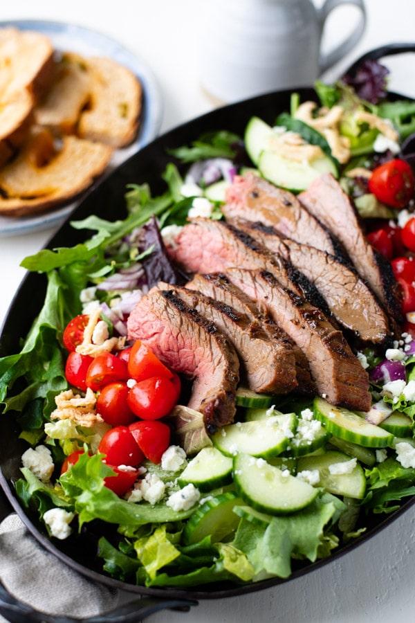 Close up side shot of grilled flank steak salad on a platter