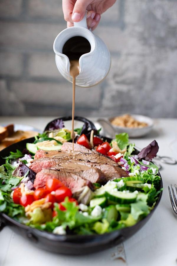 Pouring dressing on steak salad