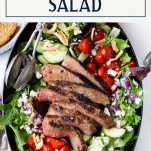 Overhead shot of warm steak salad recipe with text title box at top