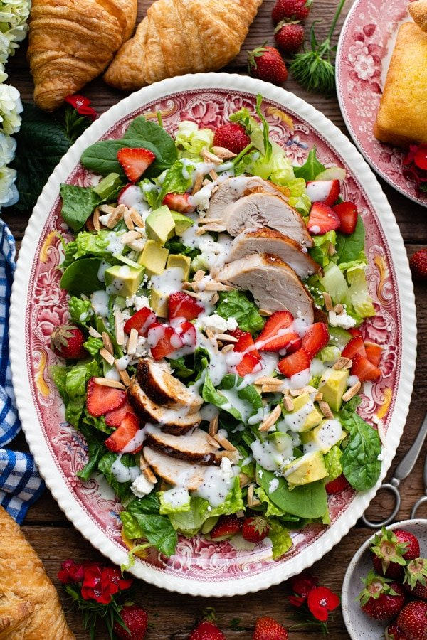 Strawberry poppyseed chicken salad on a wooden table surrounded by croissants