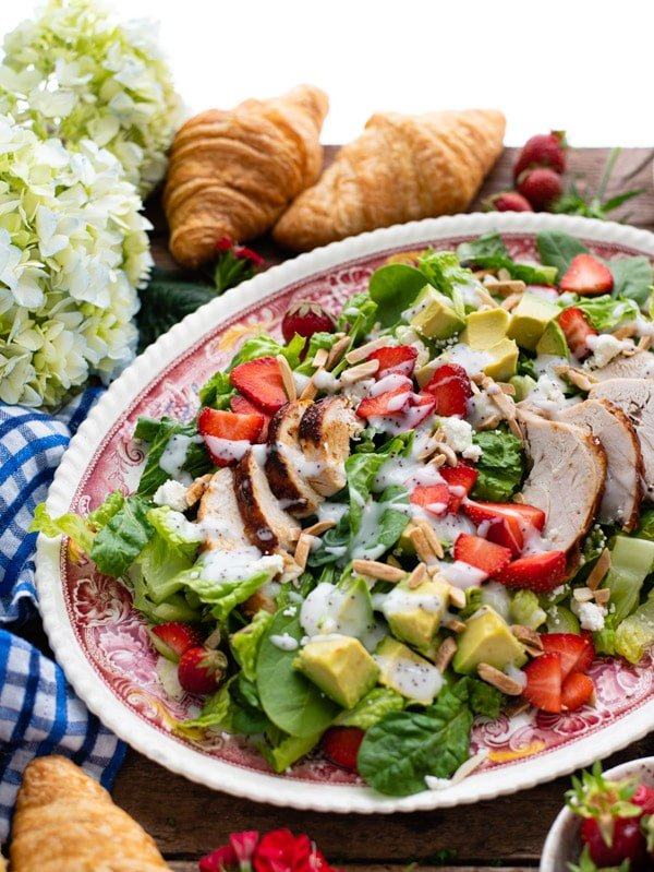Side shot of strawberry spinach salad with chicken on a serving tray