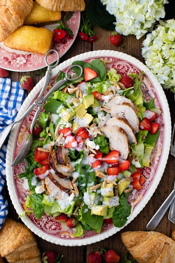 Strawberry chicken salad with feta and almonds on a red and white platter