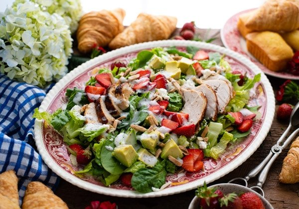 Horizontal shot of strawberry chicken salad with poppy seed dressing on a red and white platter
