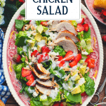 Overhead image of strawberry spinach salad with chicken and text title overlay