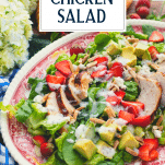 Side shot of a platter of strawberry chicken salad with text title overlay