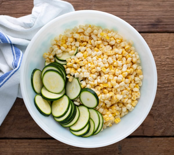Corn and zucchini in a white bowl