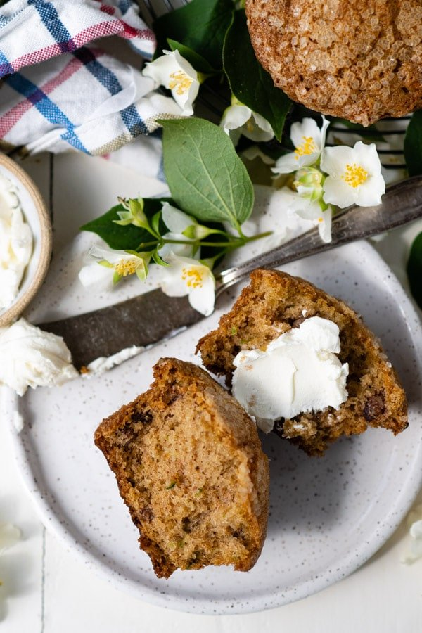 Overhead shot of sliced zucchini muffins served with cream cheese.