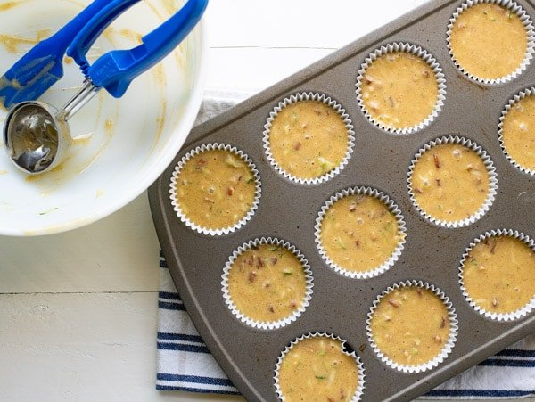 Zucchini muffin batter in a muffin tin before baking
