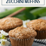 Close up side shot of zucchini muffins on a wire rack with text title box at top