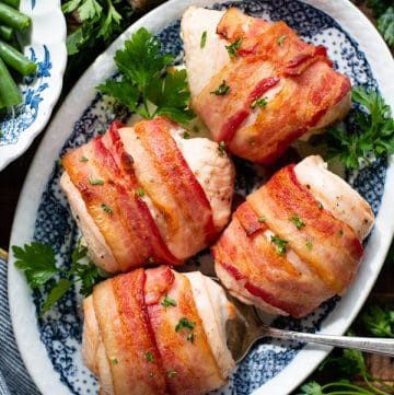 Overhead shot of a plate of bacon wrapped chicken breast on a wooden table
