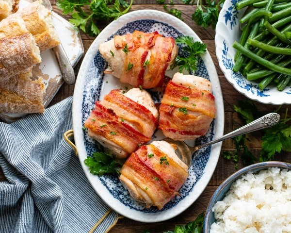 Horizontal overhead shot of a plate of stuffed bacon wrapped chicken breast