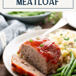 Mini meatloaf on a plate wrapped in bacon and served with sides and text title box at top