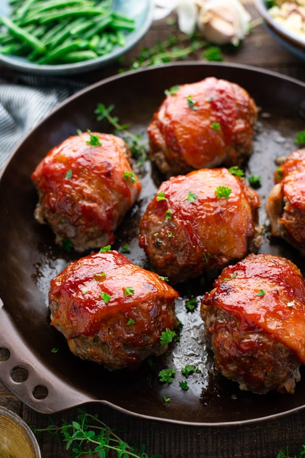 Close up shot of mini bacon wrapped meatloaf in a baking dish