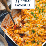 Overhead shot of cheesy ground beef noodle casserole with text title overlay