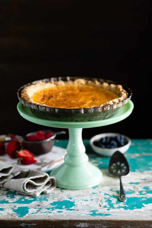 Side shot of an easy buttermilk pie sitting on a green cake stand