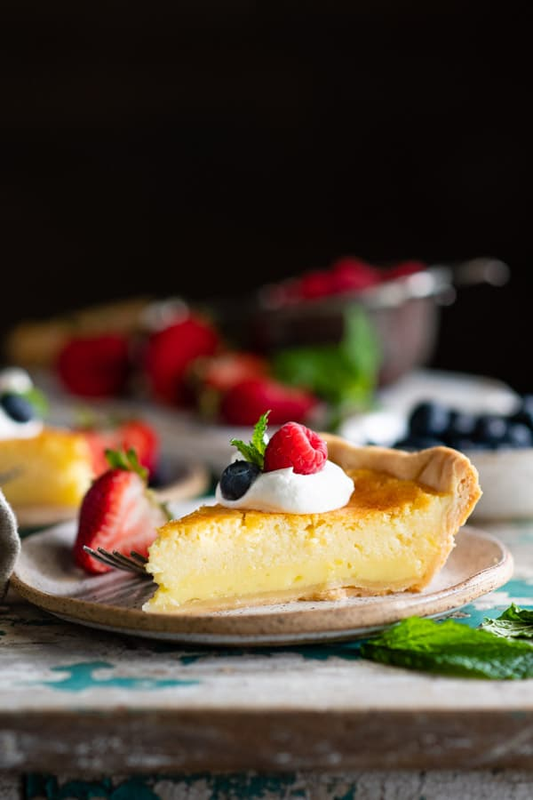 Side shot of a slice of southern buttermilk pie on a white plate with berries and fresh mint