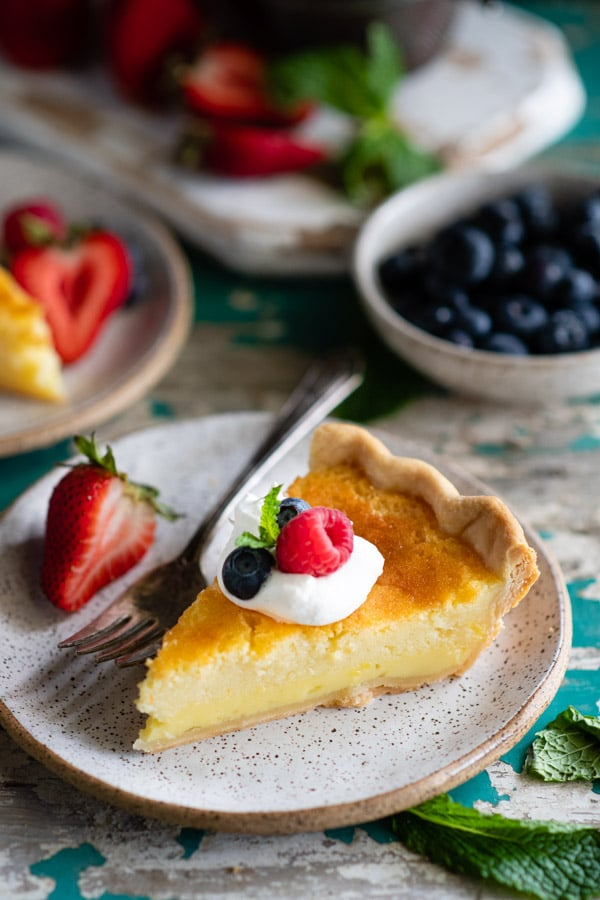Close up shot of a slice of old fashioned buttermilk pie with whipped cream and berries on a white plate