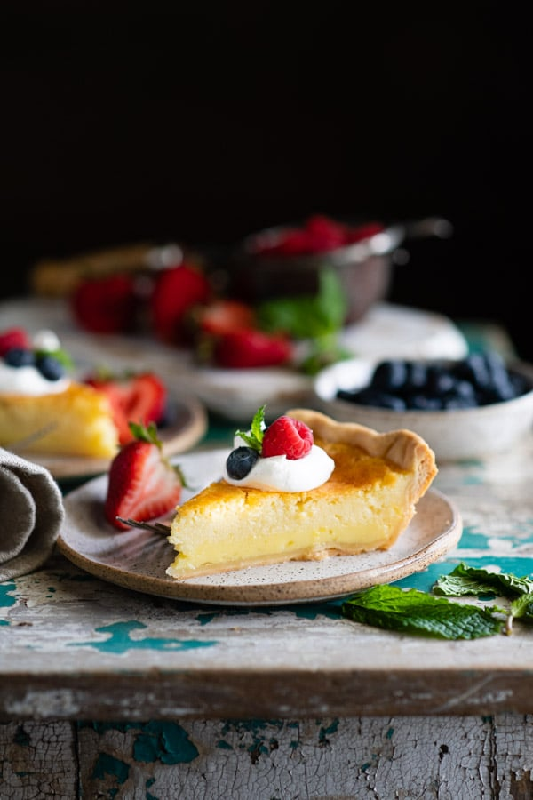 Side shot of a slice of lemon buttermilk pie on a white plate with berries and whipped cream