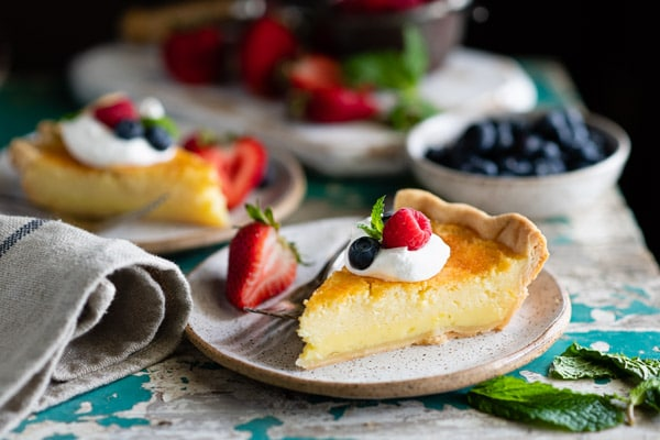 Horizontal shot of a slice of easy buttermilk pie on a rustic table