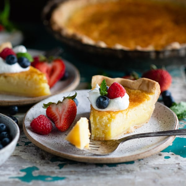 Front shot of a slice of lemon buttermilk pie with a bite on a fork