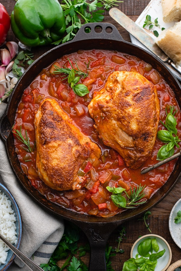 Overhead image of chicken cacciatore recipe with tomatoes vegetables wine and herbs