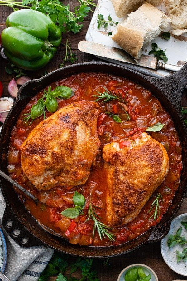 Overhead shot of chicken cacciatore in a cast iron skillet