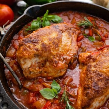 Close up shot of Italian hunters chicken in a skillet with sauce.