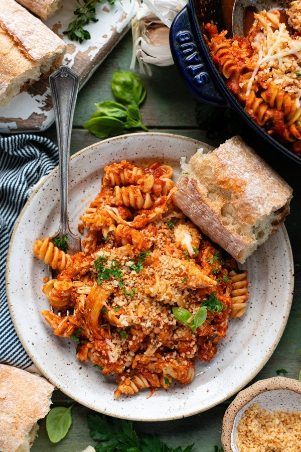 Overhead shot of a plate of baked chicken parmesan casserole with pasta