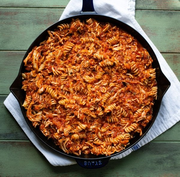 Shredded chicken tossed with pasta and marinara sauce in a cast iron skillet